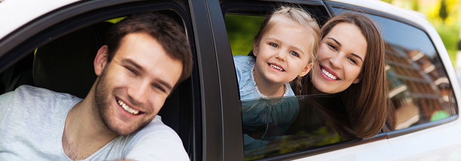 father, wife, and child in a car looking out the windows